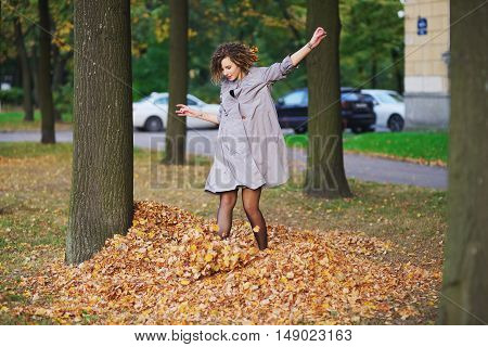 Beautiful young girl in a purple cloak with disheveled hair having fun while standing on a pile of fallen autumn leaves and kicking their feet while walking on a city alley.
