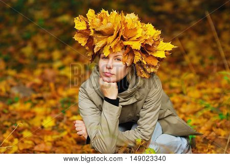 beautiful young girl in autumn park with wreath of leaves close-up.