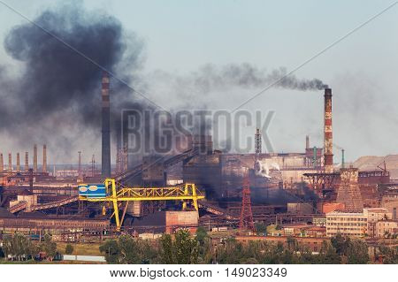 Steel Factory With Smog At Sunset. Pipes With Black Smoke