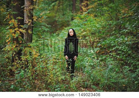 girl stands among the green forest and holding fern