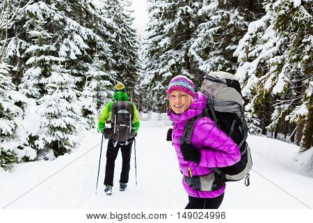 Man and woman happy couple hikers trekking in white winter woods and mountains. Young people walking on snowy trail with backpacks healthy lifestyle adventure camping on hiking trip Poland.