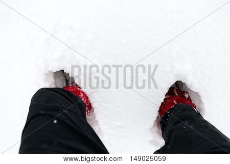 Shoes on snow in white winter forest during hiking. Hiker boots and legs on white snowy background. Travel recreation fitness and healthy lifestyle. Motivation and inspirational winter landscape.