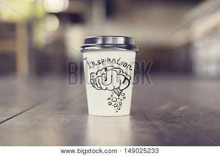 Takeaway coffee cup with brain sketch on wooden floor. Inspiration concept