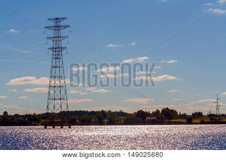 tower power plant in the water, blue sky with small clouds in the distance Beach, forest, autumn landscape, the sun shining on the water