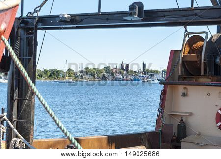 Fairhaven town center and waterfront framed by fishing boat docked in New Bedford