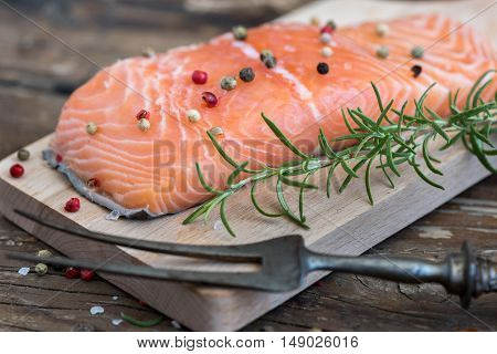Raw Salmon Fish Fillet with Fresh Herbs on Cutting Board