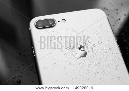PARIS FRANCE - SEP 26 2016: New Apple iPhone 7 Plus unboxing and testing - water drops on rear - studio shot. New iPhone7 is one of the best waterproof smart phone in the world