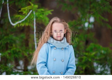 Adorable little girl in christmas forest in winter day outdoors