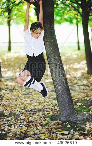 Cute young woman student caught on a branch with his hands and easily hanging on a tree pulling legs in autumn park.