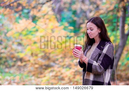 Fall concept - beautiful girl drinking coffee in autumn park under fall foliage