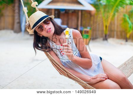 Happy young woman lying in the hammock on tropical beach