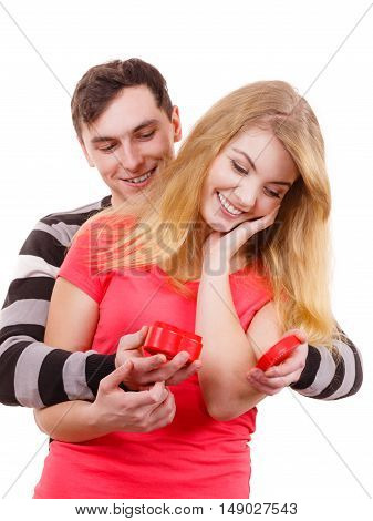 Couple and holiday concept. Handsome man surprising cheerful woman with red heart shaped gift box isolated