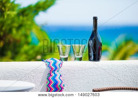 Glass and bottle of tasty red wine on balcony