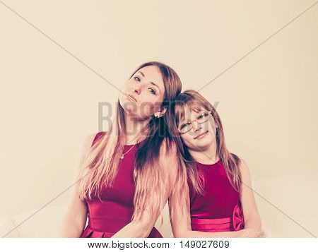 Family relationships. Beauty mother with lovely daughter spending time together. Mommy and girl child wearing elegant clothes.