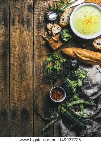 Homemade pea, broccoli, zucchini cream soup in white bowl with fresh bread on wooden serving boards over rustic background, top view, copy space, vertical composition