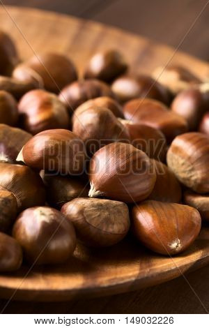 Chestnuts on wooden plate photographed with natural light (Selective Focus Focus one third into the chestnuts)