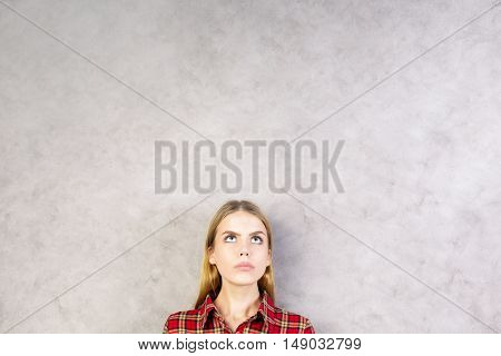 Portrait of pretty young woman on textured concrete wall background with copy space