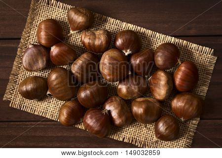 Fresh raw chestnuts photographed overhead on wood with natural light (Selective Focus Focus on the top of the chestnuts)