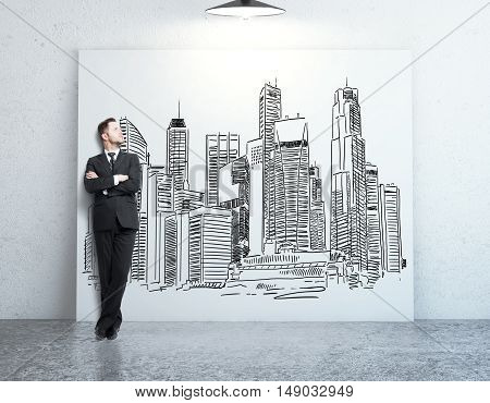 Young businessman in concrete room looking at whiteboard with creative city sketch