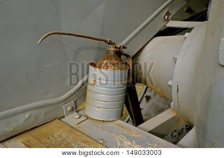 Old gray rusty oil can with a long spout in a painted gray can on the platform of a steam engine