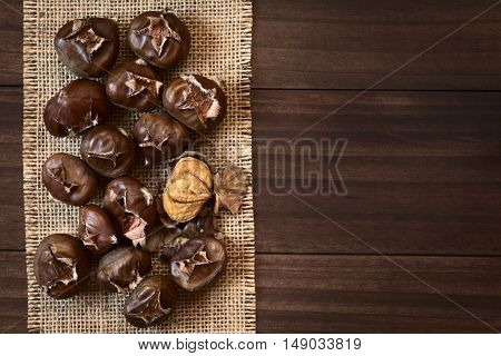 Freshly roasted or baked chestnuts photographed overhead on wood with natural light