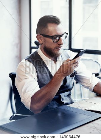 Bearded Stylish Young Man Wearing Glasses White Shirt Waistcoat Working Modern Loft Startup Process.Creative Person Using Smartphone Texting Message.Drawing Tablet Desktop Computer Wood Table Vertical