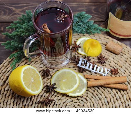 mulled wine with a lemon, cinnamon, an anisetree, a juniper and an inscription enjoy