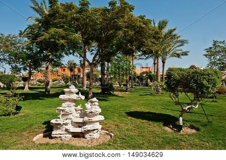Stone Monument On Garden Of Resort With Trees