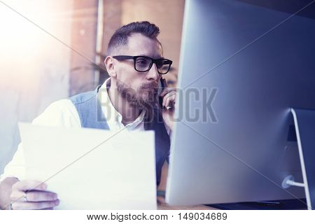Bearded Businessman Thinking Startup Business Strategy Workplace.Man Using Smartphone Call Meeting Partner Holding Papers Hand.Young Guy Wearing White Shirt Waistcoat Working Desktop.Flare Blurred