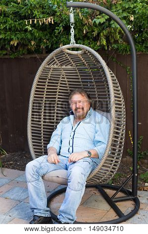 Male sitting on vintage hanging chair in the garden.