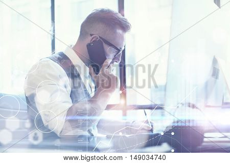 Bearded Businessman Planning Global Strategy Virtual Screen.Startup Concept Innovation Graphs Interfaces Icon.Young Man Making Great Business Idea Modern Workplace.Guy Using Smartphone Call Meeting
