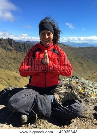 Young latin woman sitting doing yoga on a mountain top