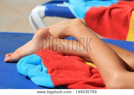 Young Child's Legs And Bright Colored Towels On A Sun Lounger In Sunshine