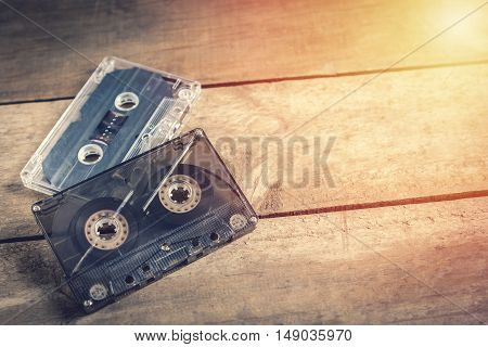 Old retro cassette tape on vintage wooden background with sunlight effect.