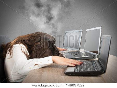 Stressed businesswoman due to overwork against laptop