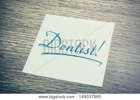 Dentist Reminder On Paper Lying On Wooden Cupboard