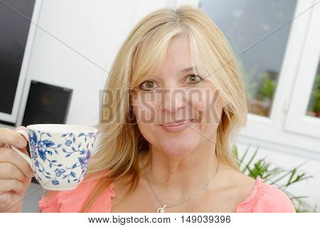 Smiling senior woman drinking tea at home