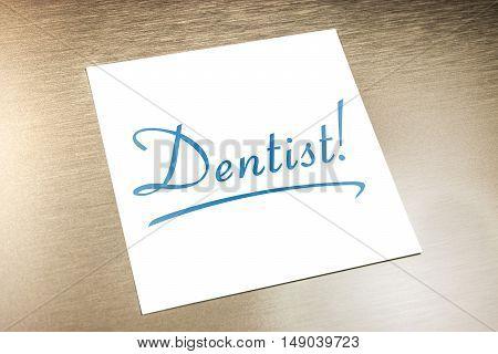 Dentist Sticky Note On Paper Lying On Golden Aluminium