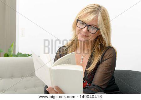 a mature blond woman reading a book