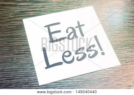 Eat Less Reminder On Paper Lying On Wooden Table