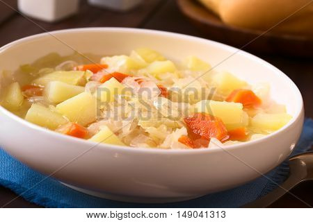 Vegetarian soup or stew made of sauerkraut carrot and potato photographed with natural light (Selective Focus Focus one third into the dish)