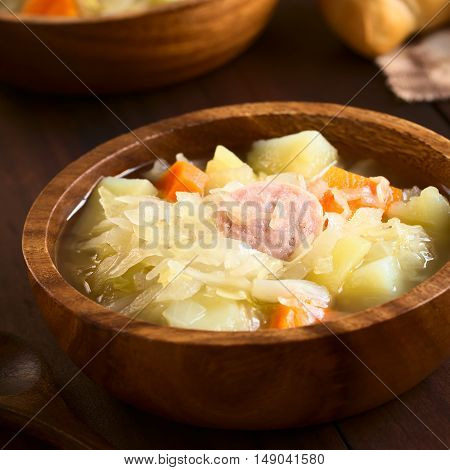 Sauerkraut soup or stew prepared with potato carrot and bratwurst served in wooden bowl photographed with natural light (Selective Focus Focus in the middle of the dish)