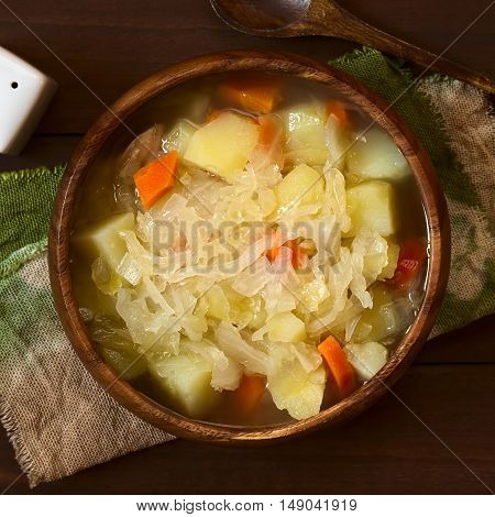 Vegetarian sauerkraut soup or stew prepared with potato and carrot served in wooden bowl photographed overhead on dark wood with natural light (Selective Focus Focus on the top of the dish)