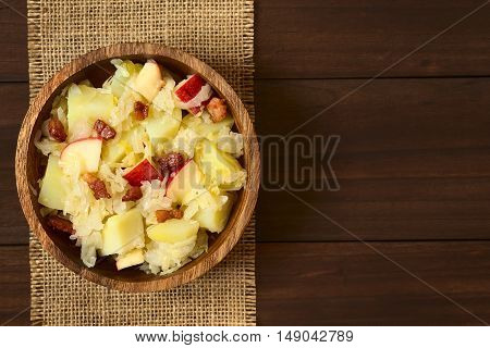 Potato sauerkraut and apple salad with fried bacon served in wooden bowl photographed overhead on dark wood with natural light (Selective Focus Focus on the top of the salad)
