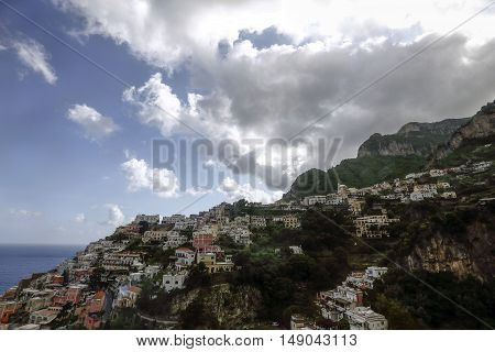 view of city of positano between mountains and mediterranean sea in italy