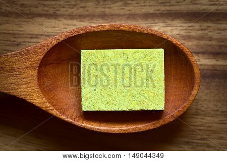 Vegetable bouillon stock or broth cube on wooden spoon photographed overhead with natural light (Selective Focus Focus on the top surface of the cube)