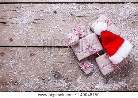 Wrapped christmas presents and decorative Santa hat on aged wooden background. Selectife focus. Top view. Place for text.