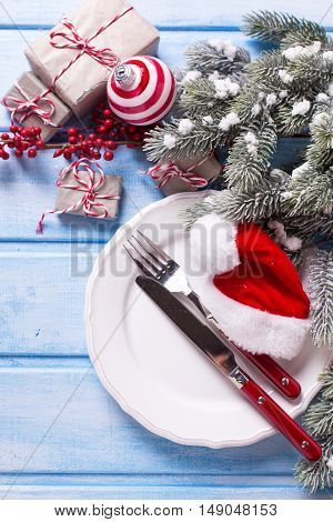 White plate knife and fork christmas decorations in white and red colors on blue wooden table. Top view. Selective focus.