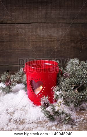 Candle in red lantern and branches fur tree on aged wooden background. Christmas composition. Selective focus. Vertical image. Place for text.