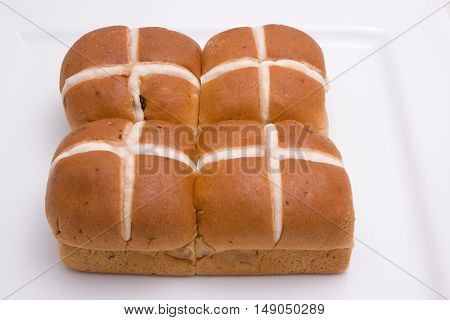 Four Hot Cross Buns on a white plate